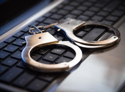 handcuffs on top of a laptop